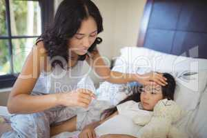 Mother checking body temperature of sick daughter in bed room