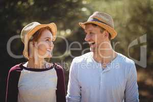 Cheerful young couple wearing hat on sunny day