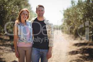Smiling young couple standing at olive farm on sunny day