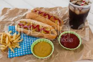 Hot dog, sauces and cold drink on brown paper