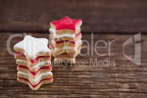 Red and white sugar cookies stacked on wooden table