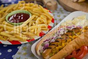 Hot dog and french fries on wooden table with 4th july theme