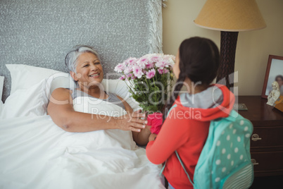 Granddaughter giving flowers to grandmother in bed room