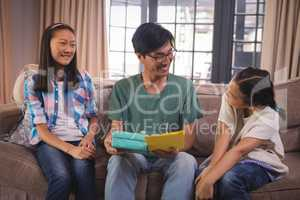 Father receiving greeting card and gift box from siblings in living room