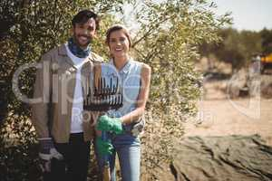 Smiling young couple holding rake at olive farm on sunny day