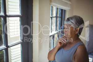 Thoughtful senior woman looking through window in bed room