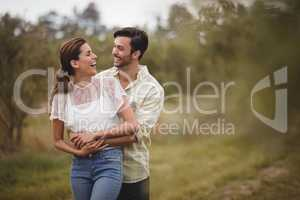 Cheerful couple standing on field at olive farm