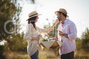 Happy young woman feeding boyfriend at farm