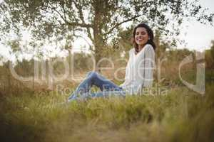 Smiling young woman sitting on grassy field at farm