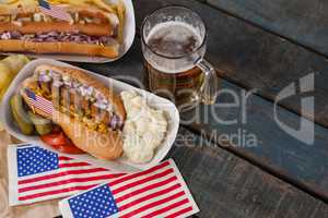 Hot dog and glass of beer with american flag on wooden table
