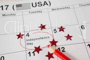 Red colored pencil with fourth of july calendar