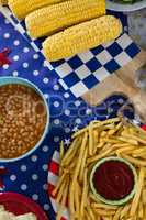 French fries and corn cob on wooden table with 4th july theme