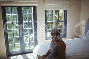 Senior woman reading book while sitting on bed in the bed room