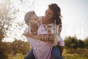 Young man piggybacking woman at farm during sunny day