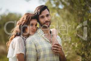 Loving young couple standing together at farm