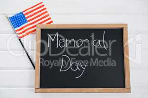 Slate with text and an American flag on wooden table