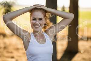 Smiling young woman exercising on sunny day at farm