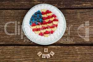 Date blocks and fruitcake on wooden table with 4th july theme