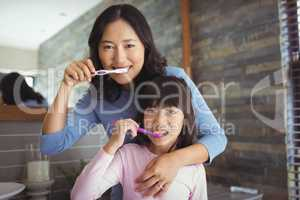 Mother and daughter brushing teeth in the bathroom
