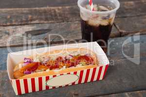 Hot dog and cold drink on wooden table