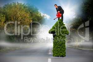 Composite image of businessman watering with red can