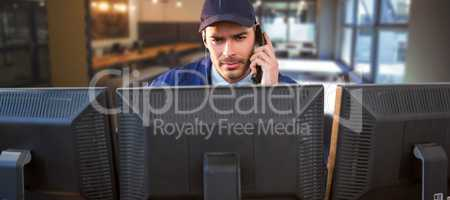 Composite image of security officer talking on phone while using computer at desk
