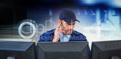 Composite image of security officer listening to earpiece while using computer at desk
