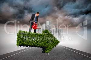 Composite image of businessman holding red watering can
