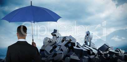 Composite image of rear view of businessman carrying blue umbrella