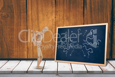Composite image of wooden 3d figurine standing with hands on back
