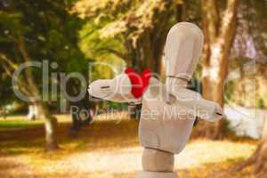 Composite image of wooden 3d figurine standing and holding a red heart in front