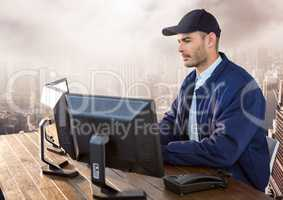 Security man on computer over large city
