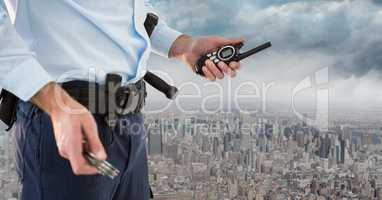 Security guard lower body with walkie talkie against skyline and clouds
