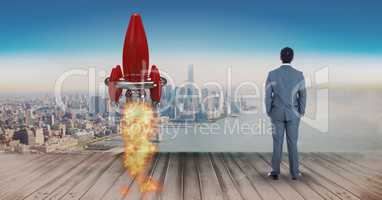 Digital composite image of businessman standing by rocket launch on pier while looking at sea and ci