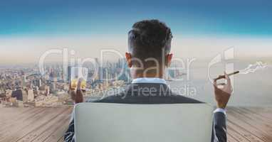 Rear view of businessman sitting on chair with glass of alcohol and smoking cigar while looking at c