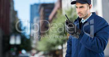 Security guard with walkie talkie against blurry street