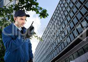 Security guard holding walkie talkie standing in city