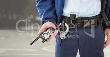 Security guard lower body with walkie talkie against blurry street