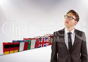 main language flags suitcases behind young businessman thinking