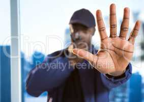 Security guard with walkie talkie and hand in front against blurry window showing city