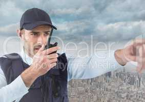 Security guard with walkie talkie pointing against skyline and clouds