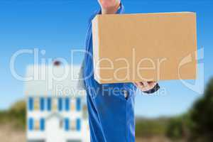 Deliver wearing a overall is holding a package against house background