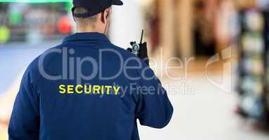 Back of security guard with walkie talkie against blurry shopping centre