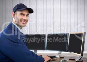 Security guard smiling in front of the computers with white wood background