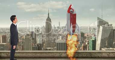 Digital composite image of businessman looking at  rocket launch in city