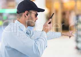 Security guard with walkie talkie pointing against blurry shopping centre