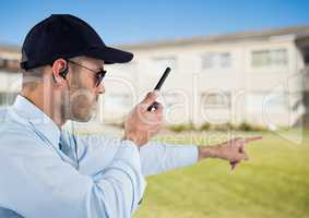 Security guard holding walkie talkie and gesturing while standing on field
