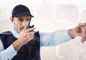 Security guard with walkie talkie pointing against faded skyline