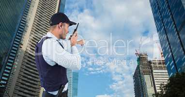 Security guard talking on walkie talkie and gesturing while standing by buildings against sky
