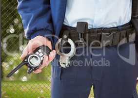 security guard with walkie-talkie on his hand and cuffs on the belt in front of the fence